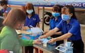 土龍木市共青團員向參加天后宮廟會 群眾派發口罩以防控疫病。
