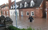 英國西部滕伯里威爾斯特梅河決堤造成街道淹水,一名男子週日涉水越過道路。(圖源:AFP)