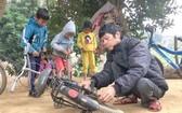 范維勇為遍遠鄉村的學生修理自行車。