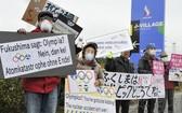 """日本聖火傳遞起點民眾遊行抗議""""重建奧運""""。(圖源:共同社)"""
