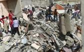 救援人員在居民樓倒塌事故現場救援。(圖源:AFP)