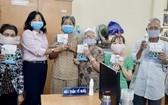 陳月梅主席(左二)向人民贈送口罩。