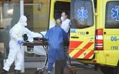 新冠疫情在荷蘭快速蔓延,救援人員送患者上救護車。(圖源:路透社)