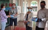 本報副執行編輯陳月寶(左一)代表向報販贈送口罩。