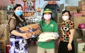 梁柳嬋(左)與弟婦向勞動人家贈送禮物。