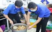 志願青年烹煮飯菜並贈送給貧困者。