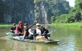 遊客乘小船遊覽觀光寧平省長安生態旅遊區美景。(圖源:互聯網)