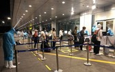 從美國加州撤回的同胞抵達廣寧省雲屯機場時辦理健康申報手續。(圖源:VNA)