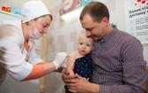 一名嬰兒被父親抱在懷中,接受護士接種的第一劑麻疹、腮腺炎和風疹三聯疫苗。(圖源:Unicef)
