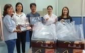 本報工會副主席陳月寶(左一)代表工會接收禮物和派發給有少兒子弟的工會會員。