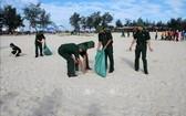 廣治省由靈縣青年官軍、士兵及共青團員在沙灘上撿拾垃圾,攜手保護環境。(圖源:越通社)