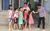 崇華華文中心老師向每班學生測量體溫。