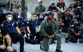 警察和遊行民眾跪地抗議針對非裔男子暴力執法的行為。(圖源:路透社)
