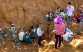 職能力量和烈士親屬發掘17名特工犧牲的集體墓穴。(圖源:德誠)
