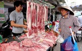 一名消費者在傳統市場選購鮮豬肉。(圖源:田升)