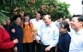 阮春福總理(前右三)同北江省米脂荔枝產量最多地區的同胞交流。(圖源:VGP)