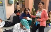 華人商販應氏蓮(右)向視障者派發營養餐。