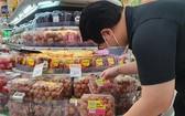 一名新加坡消費者在當地超市選購越南荔枝。(圖源:越通社)