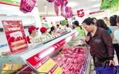 消費者在超市選購豬肉。(圖源:越勇)