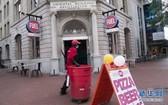 7月17日,在美國首都華盛頓,一名清潔工經過一家重新開業的餐館。(圖源:新華社)