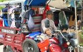 四隱先生駕著載滿衣服的電動三輪車走遍各條大街小巷去派發。