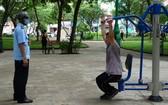 防疫工作人員提醒一名在黎文八公園鍛煉身體的市民應佩戴口罩。(圖源:何安)
