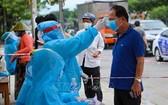 防疫工作人員給峴港市五行郡市民測量體溫。(圖源:越通社)