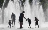 在法國東部城市科爾馬,一家大小在地面噴泉上淋水消熱。(圖源:AFP)