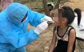 防疫工作人員向一名女童進行咽喉拭子取樣測試。(圖源:進一)