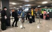 從美國撤回的我國公民在機場排隊等候辦理登機手續。(圖源:外交部)