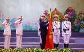 政府總理阮春福代表黨及國家領導為越南人民公安傳統旗幟上佩掛一等軍功勳章。(圖源:杜忠)