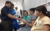 市勞動聯團代表向受疫情影響的女工人派發補助金。(圖源:L.T)
