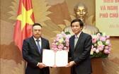 新任國會辦公廳副主任陳士清(左)從國會辦公廳主任、國會秘書長阮幸福阮幸福手中接過人事委任《決定》。(圖源:中成)