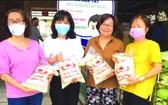 華人商販應氏蓮(右一)與各商販在準備向貧困者派發大米。
