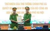 公安部副部長黎貴王(右)向河內市公安廳頒授政府總理簽發的表彰信及獎狀。(圖源:首都安寧報)
