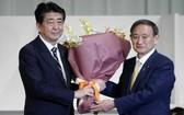 日本內閣官房長官菅義偉(右)當選自民黨新總裁後向安倍晉三獻花。(圖源:AFP)
