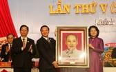 國家副主席鄧氏玉盛(右)向慶和省政治學校贈送胡伯伯肖像。(圖源:越通社)