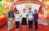 郡勵學會主席李金梅(右一)、常值副會長林晉章(左一)向3名市級優秀生頒發獎學金。