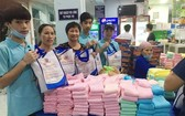 華人商販應氏蓮(左三)與志願者準備慈善禮物。