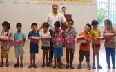芽莊廣東會館理事長鄭成龍給小朋友派發月餅。
