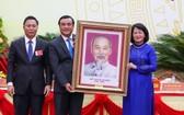國家副主席鄧氏玉盛(右)向廣南省贈送胡伯伯肖像。(圖源:清德)