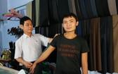 范勇(左)為顧客量身定制衣服。