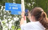 一名女遊客拍攝黎筍街名指示牌,以進一步了解該街名的歷史資訊。(圖源:明君)