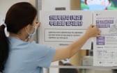 韓國世宗一間醫院的職員正在醫院入口處張貼告示,提醒民眾流感疫苗接種計劃暫停。 (圖源:路透社)
