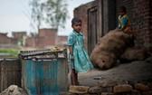 印度北方邦的貧民窟,兒童在一家金屬拋光工廠外玩耍。(圖源:聯合國)