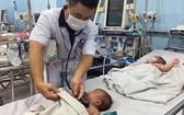 市第一兒童醫院醫生在給一名入住醫院重症監護室接受治療的手足口病童查體。(圖源:舒英)