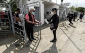"""10月25日,在智利首都聖地亞哥一處投票站,一位老人在入口給手消毒。 智利25日舉行全民公投,選民們投票贊成成立""""制憲會議""""制定新憲法。(圖源:新華社)"""