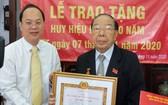 市委副書記、市委組織處主任阮胡海向阮文志同志(右)頒授60年黨齡紀念章。(圖源:梅花)