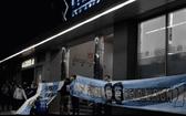 """大批馬拉多納的粉絲聚集在診所門口舉著印有馬拉多納頭像和""""加油,馬拉多納!""""字樣的橫幅。(圖源:互聯網)"""