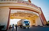 一輛運載貨品的集裝箱卡車經勞保國際口岸通關後運往老撾。(圖源:江阮)